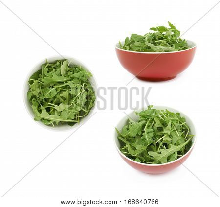 Red ceramic bowl full of rocket salad leaves isolated over the white background, set of three different foreshortenings