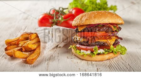 Home made hamburger with lettuce, cheese, beef meat and french fries placed on old wooden table