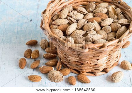Almonds, peeled kernels and whole nuts, in a wicker basket on old wooden table.