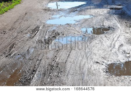 Bad Road. Close up on Puddle. Pot hole or pothole image with a dirty water puddle as a transportation symbol of road maintenance and car insurance risk to auto suspensions.