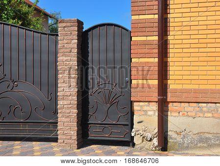 Outdoor house door and gate installation. Close up on entrance metal door.