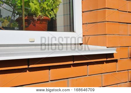 Plastic window with white metal sill. Brick House Wall