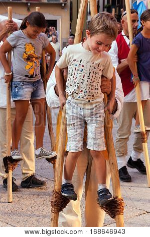 VERONA ITALY - SEPTEMBER 24 2011: Tocati International festival of street games. The instructors of the Schieti village (Urbino Italy) teach a young boys to stay balanced on wooden stilts