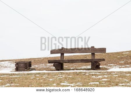 Wooden bench and trash can in the park at winter time