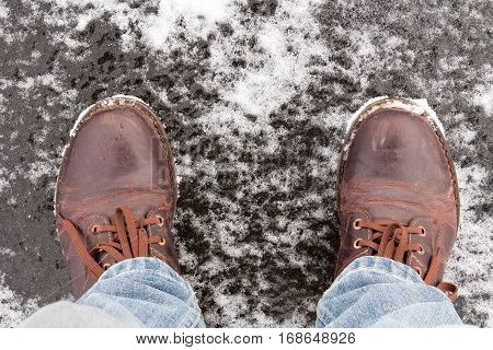 Male legs in leather shoes standing on frozen lake ice
