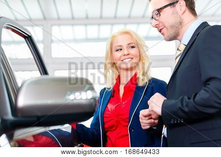 Woman looking at car in auto dealership