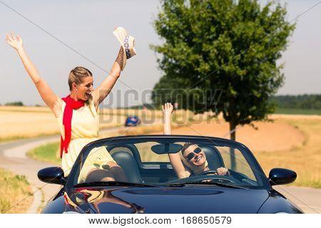 Best friends having summer joyride in convertible car passing a field