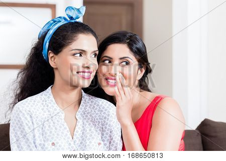 Young woman whispering to her best friend gossips or funny secrets indoors