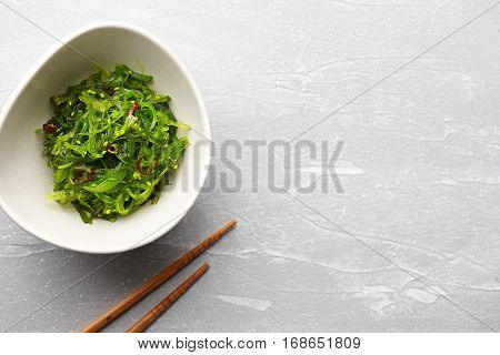 Japanese chuka wakame salad with seaweed and sesame seeds on stone background
