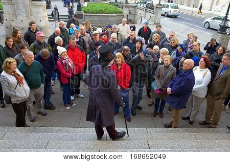 London, England - December 28, 2015: A man in a top hat and coat addresses a crowd of people as part of guided tour in Threadneedle Street, London