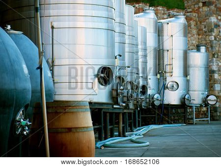Eight stainless steel made wine brewing tank and a wood barrel