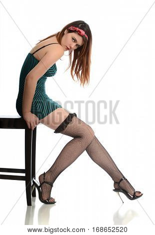 Young woman wearing a teal dress and high heels isolated on a white background
