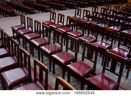 Closeup on many rows of red empty chairs in a church