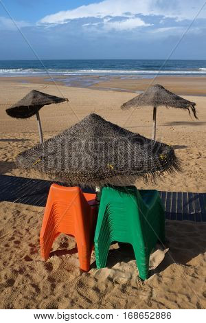 Two pile of green and orange plastic chairs next to a sun shade in an empty beach