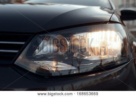 Luminous front dipped beam headlights cars close up