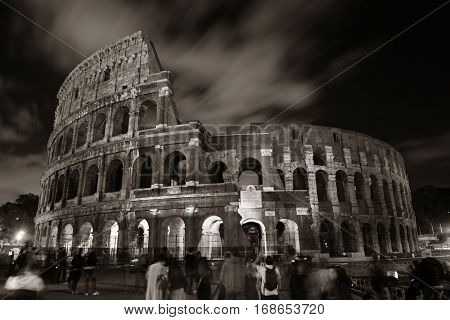 Colosseum at night with tourists, the world known landmark and the symbol of Rome, Italy.