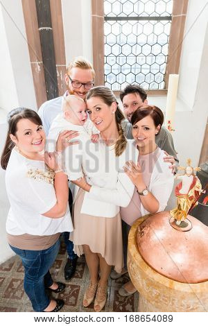 Parents and godparents stand at the baptismal font with the baby in a church