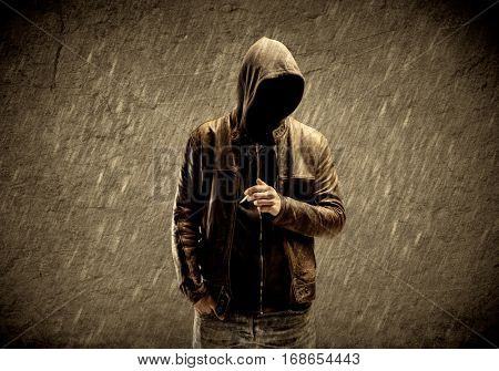 A strange suspicious confident hacker standing with a hoodie and leather jacket in front of sepia brown urban concrete wall concept