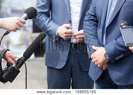 Reporters making interview with businessman, politician or spokesman. Press conference.