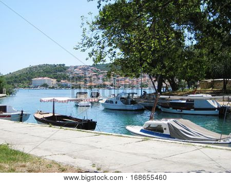 Small boats at local marina water front in historical european small town. Sunny summer day scene with blue clear sky and sea background. Recreation, relax, travel, vacation concept with empty copyspace