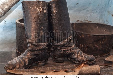 Old worn dusty boots in a rustic interior