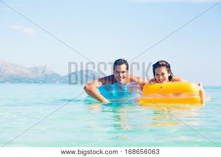 young couple with pool raft, having fun in the mediterranean sea