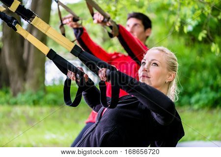 Sporty couple at sling trainer doing fitness