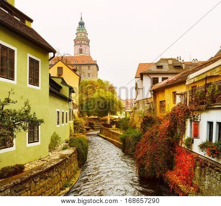 Cesky Krumlov - a famous czech historical beautiful town, view to the city river and beautiful autumn street with cjlorful buildings and chapel. Travel european background