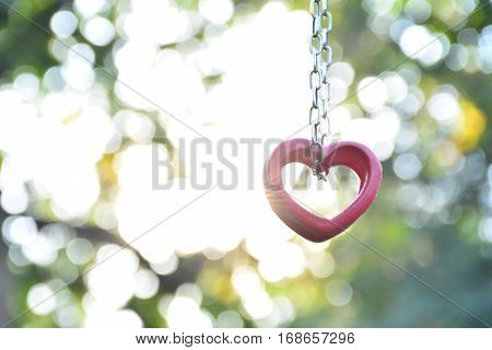 Red wood heart and chain for love on sunlight and nature background