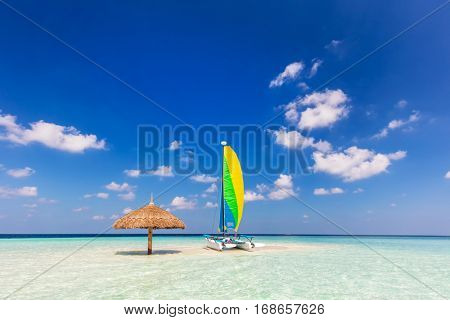 Catamaran on tropical sandbank island with sunshade umbrella. Indian Ocean, Maldives. Blue sunny sky