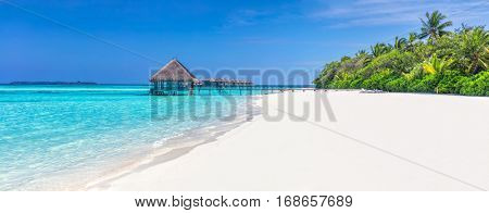 Panorama of wide sandy beach on a tropical island in Maldives. Coconut palms and water lodge on Indian Ocean.