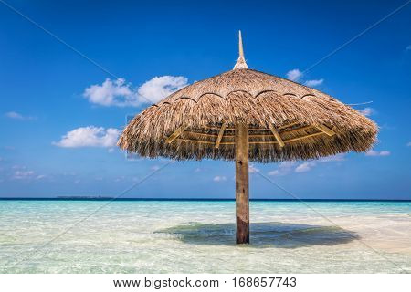 Tropical sandbank island with sunshade umbrella. Indian Ocean, Maldives. Blue sunny sky
