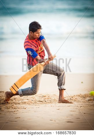 GALLE, SRI LANKA - JAN 14, 2015: Srilankan boy playing cricket. o the beach. Cricket is the most popular game in Sri Lanka.