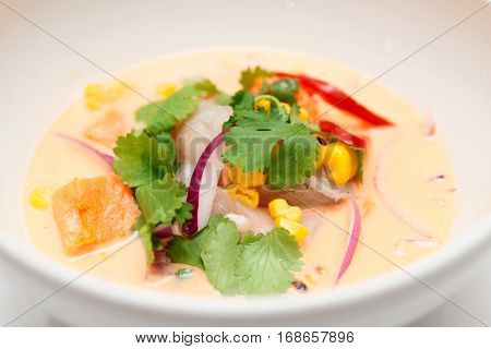 Sea bass ceviche with pumpkin, cilantro, corn and onion in deep plate, Peruvian food