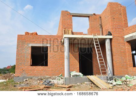 KIEV UKRAINE - JANUARY 29 2017: Residential house building construction process. New brick building unfinished house construction with doorway columns.