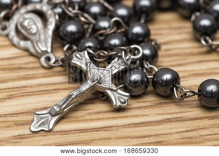 A rosary with a crucifix on wooden background