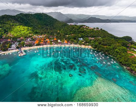 Aerial shot of the tropical bay with sandy beach, boats and buildings. Village of Padang Bai, Bali, Indonesia