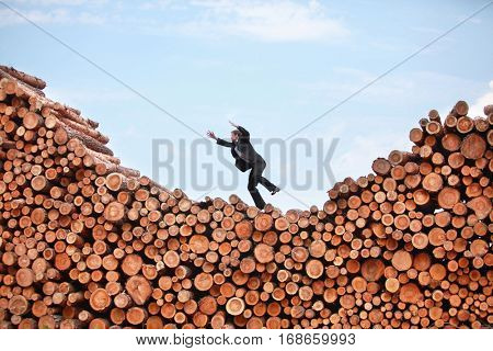 Metaphor - jumping business man on his way to the top of large pile of logs
