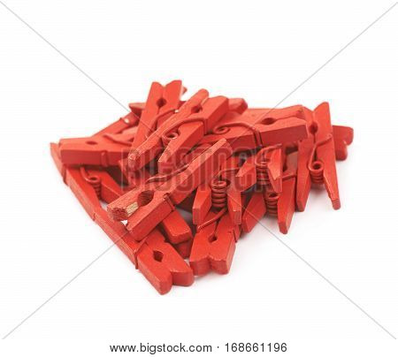 Pile of red painted wooden clothespins isolated over the white background