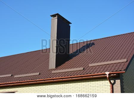 New brown metal tiled roof with plastic rain gutter system chimney house roofing construction exterior.