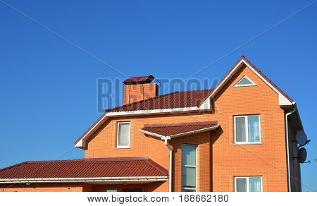 New Modern Brick House Facade Exterior. Modern House Construction. Hip and Valley roofing types.