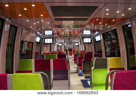 Interior of a modern european economy class fast train interior. Modern train comfortable colorful chairs. Contemporary train interior. Empty seats. Inside of high speed train compartment.
