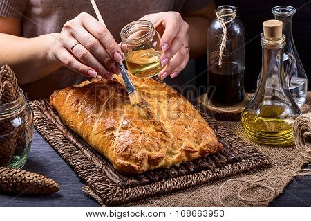 Pie on a brown background. Pie grease with olive oil. Grease the pie with a brush