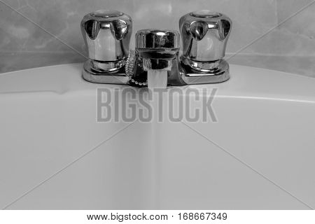 Old fashioned sink and faucet with water running into clean basin stopper chain visible