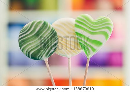 Round and heart shaped large lollipops. Three delicious lollipops against blurred background.