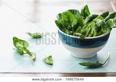 Spinach leaves in a small bowl with leaves beside bowl
