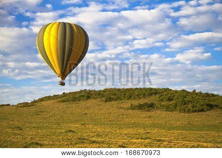 A colorful hot air balloon soars across the landscape of Kenya's Masai Mara National Park