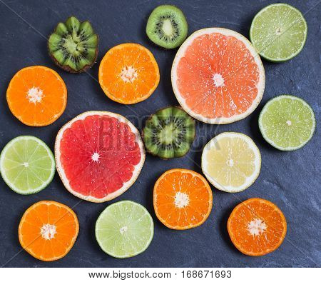Raw fruit rich in vitamin C on the black slate platter: oranges, grapefruits, lemons, limes, kiwi slices