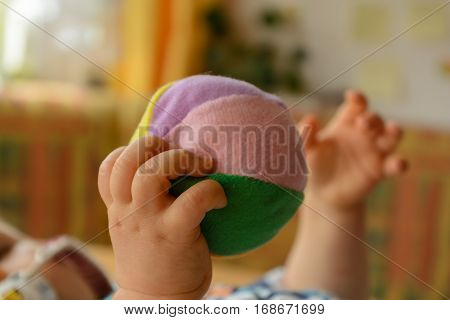Baby hands playing with a softball - close-up