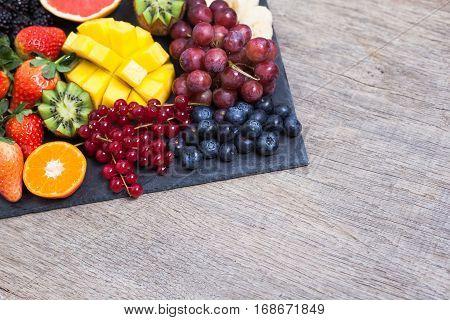 Raw fruit and berries platter mango kiwis strawberries blueberries blackberries red currants grapes selective focusview
